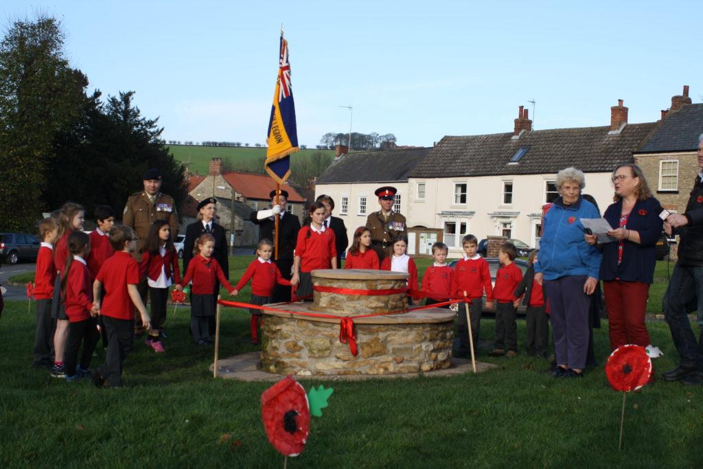 Pupils and members of British Legion circle around the centenary bench
