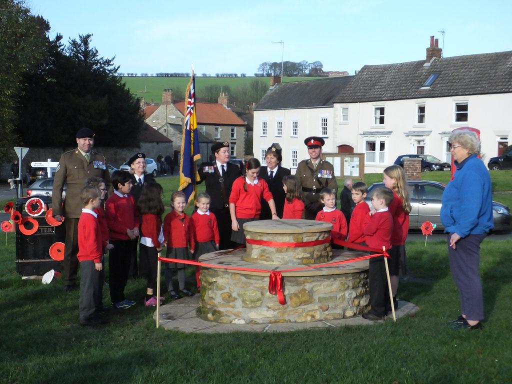 children and Royal British legion behind bench