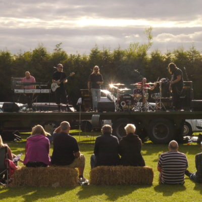 Band With People On Straw Bales In Front