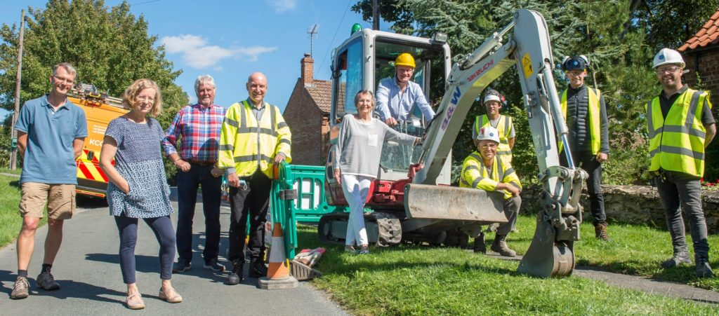 photo of Graham Stuart in digger, Gavin Steward, Councillor, residents and KCOM engineers as they work on Townside Road in Newbald